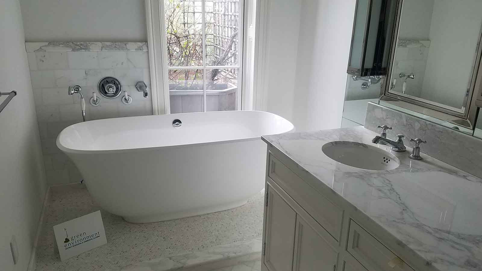 Tub on tile floor with marble wall and counter.
