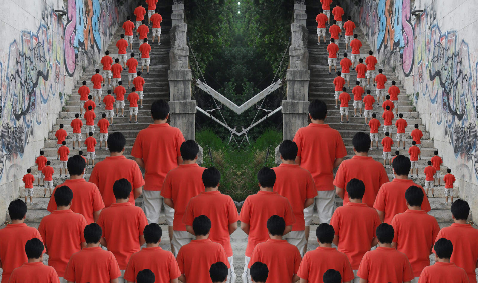 Mirrored image split down the center of a stair case covered in graffiti with the repeating image of a figure wearing a red shirt ascending the staircase.