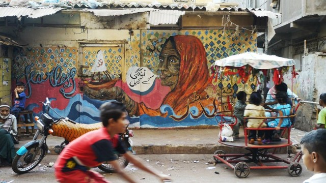 "In this Karachi mural, an old woman holds out a boat in her hand, a tribute to the area's history as an important shipping port. The text reads ""zindagi ke khel"" (the games of life)."