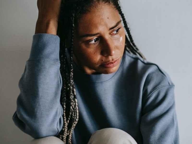 regretful black woman crying on floor