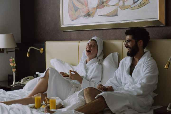 couple laughing while sitting on bed