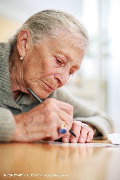 Women accepting aging -- this woman writes contentedly.  Photo courtesy of Konstantin Sutyagin