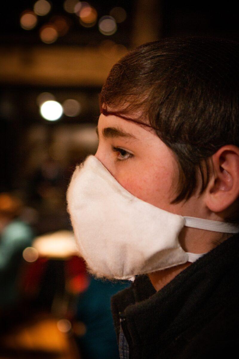 man in black shirt wearing white face mask