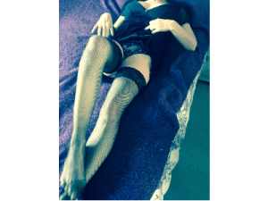 Posy in LBD pulled up to show fishnet stockings
