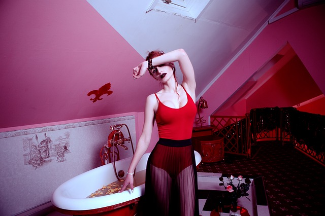woman in red body and sheer skirt in front of a bath full of rose petals