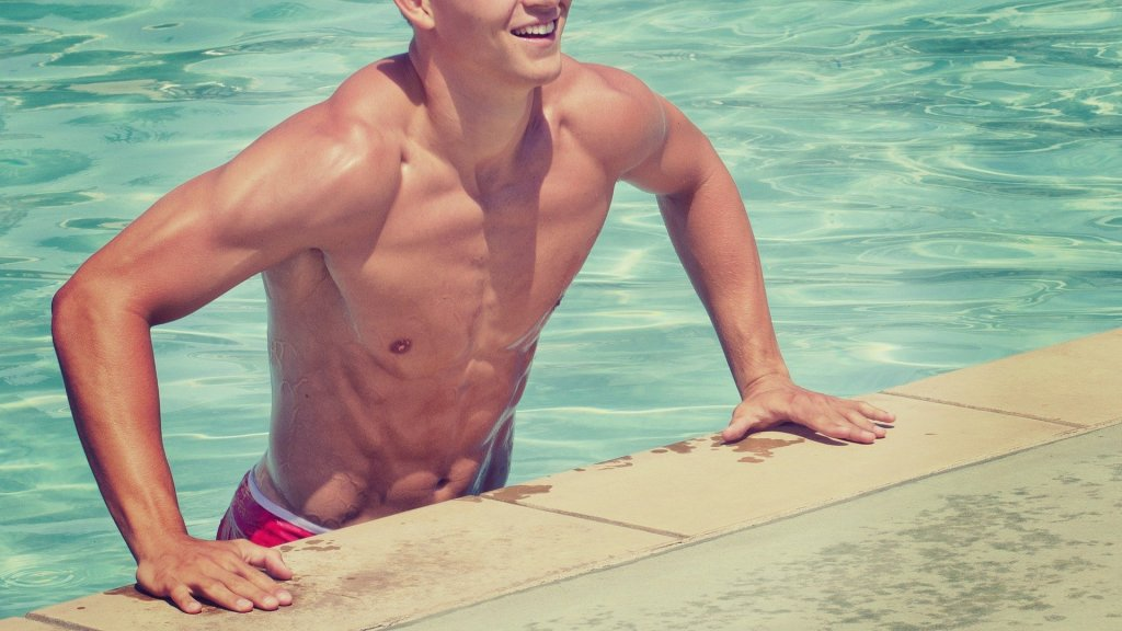 young man in swimming trunks at edge of pool