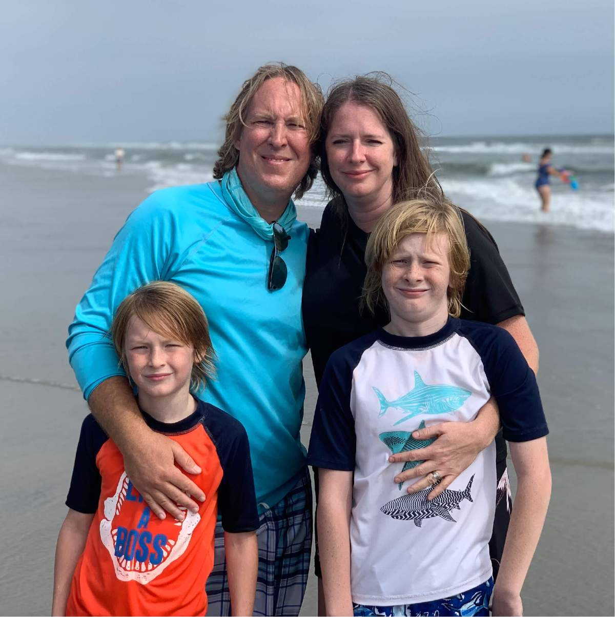 Gregory with his wife and two children posing on the beach