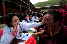 A doctor gestures as she gives a medical check to a Tibetan monk at Mindrolling Monastery as part of a medical expert volunteer project, Zhanang county