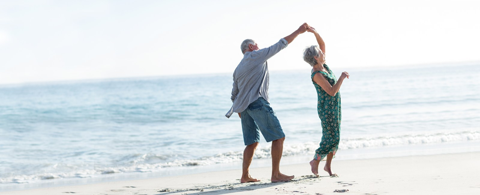 husband and wife dancing on the beach