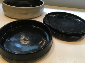 serving dish on the left, two plates stacked on the right
