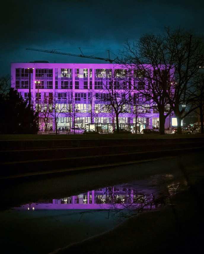 Potsdamer Bildungsforum spiegelt sich bei Nacht in einer Pfütze