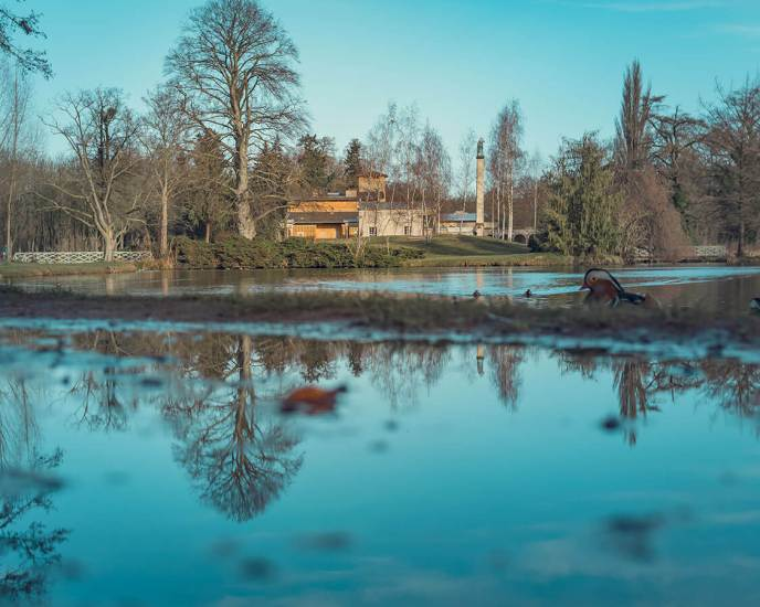 Die Römischen Bäder spiegeln sich in einer Pfütze, dahinter liegt der kleine Teich.