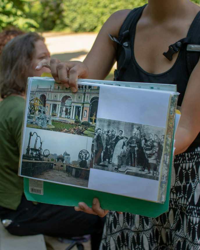 Anna von Postcolonial Potsdam zeigt uns Bilder von den astronomischen Instrumenten, die vor dem Orangerieschloss standen.