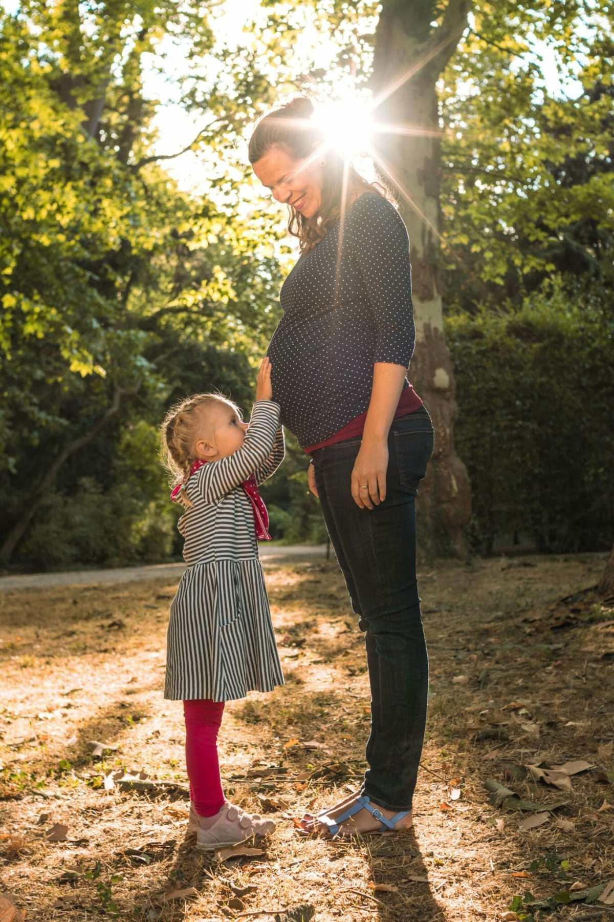 Babybauchshooting mit Mutter und Tochter, im Hintergrund Sonnenstrahlen