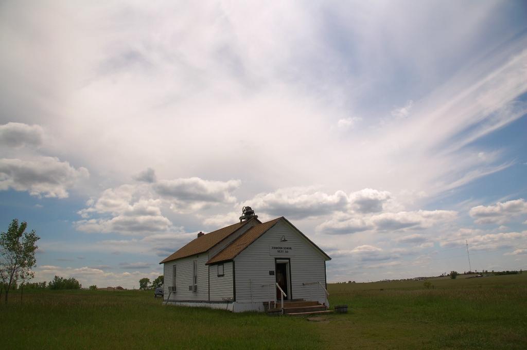 The schoolhouse with a wonderful prairie sky behind it.
