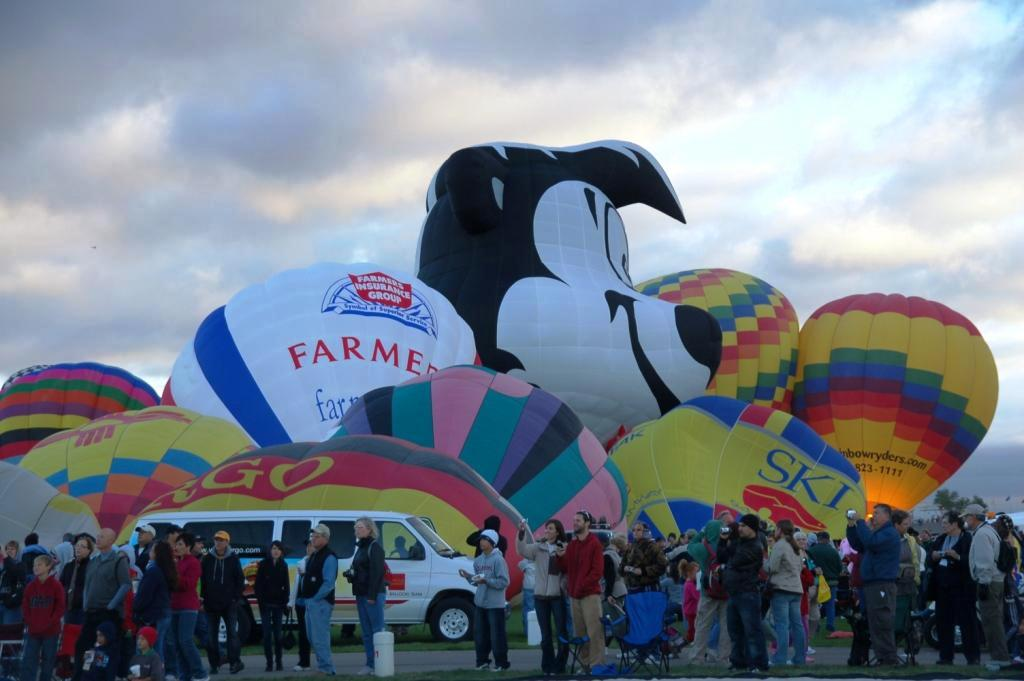 "One of my favorite things to see is just ""piles"" of balloons as they are inflating. (Note the sun still hasn't come up. We have a mountain that obscures sunrise, and there was a large cloudbank emanating from that as well that day, so we got an extra late sunrise."