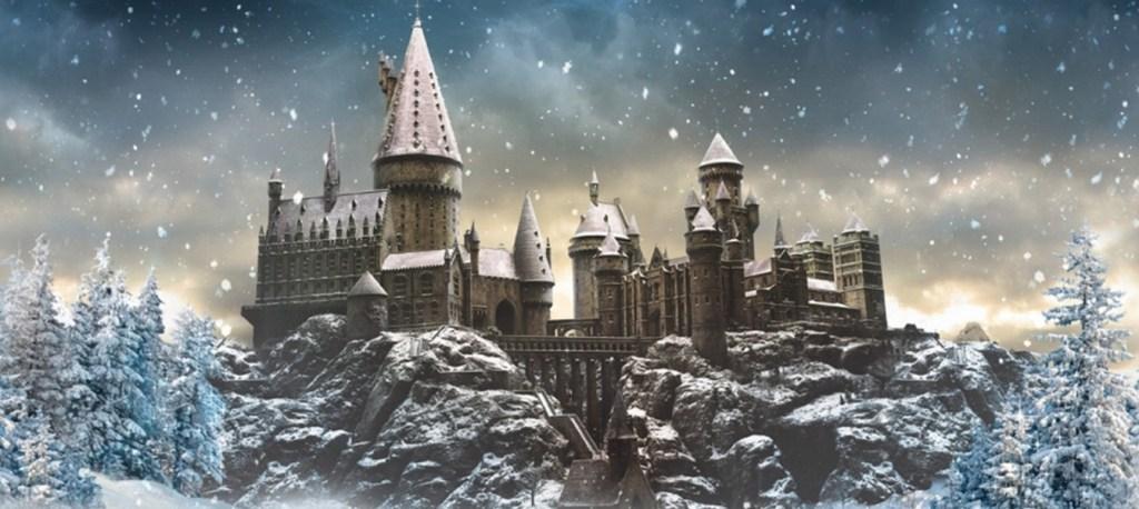 Pohled na celý hrad Bradavice se zasněženými střechami, skálou, na níž hrad stojí, a zasněženými jehličnany v okolí. Z modro-žluté oblohy (patrně svítá) sněží.