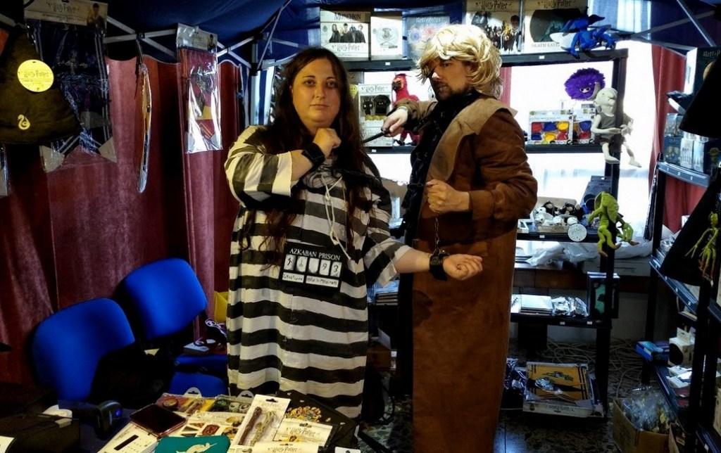 Na fotografii jsou dva coyplayeři. Vlevo je Bellatrix ve vězenském mundúru a vězenskou cedulí kolem krku. Za řetěz ji z pravé strany tahá Pošuk Moody, který ještě pravou hůlkou na Belallatrix míří.