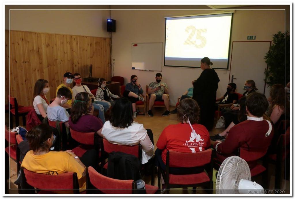 Na fotografii je zachycena třída, ve které je kruh lidí sedících na židlích. Nad nimi je plátno k promítání.
