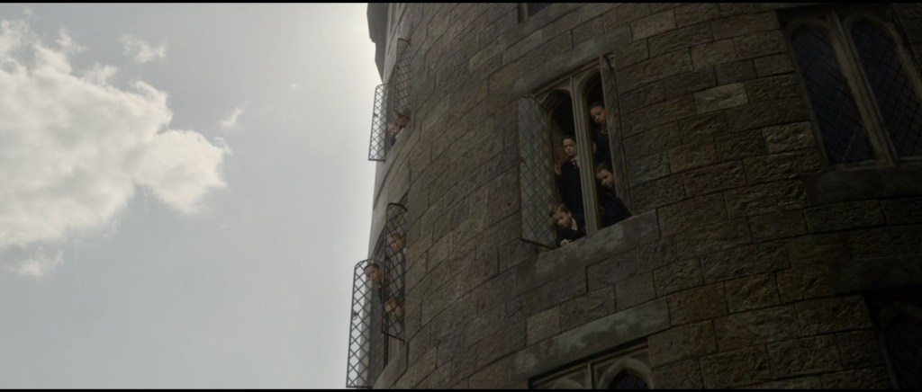 Záběr na velkou bradavickou věž. Z otevřených oken vykukují studenti.
