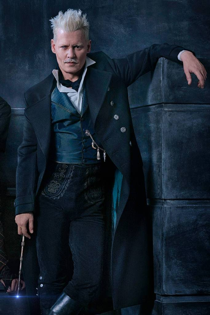 Grindelwald opřený o zeď se svěšenou pravou rukou v níž drží Bezovou hůlku.
