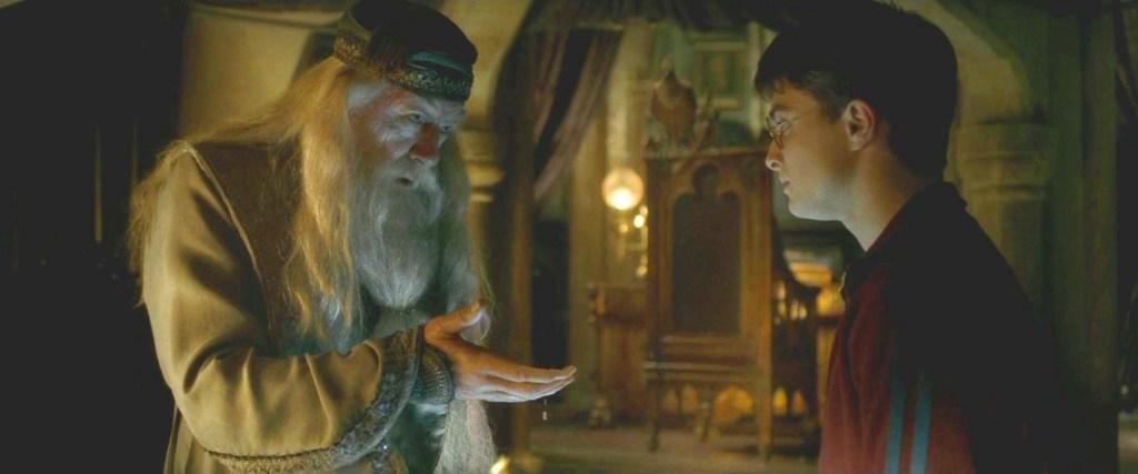 """Harry a Brumbál jsou v ředitelně na Harryho """"soukromých lekcích"""" o Voldemortově minulosti. Brumbál vlevo na obrázku se dívá na Harryho v tmavě červené mikině a kyne mu pravou rukou."""