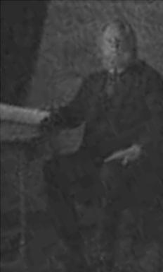 Černobílá a nepříliš ostrá fotografie Brumbálova otce, který sedí na židli. Pravou ruku má položenou na stole, na němž  je pravděpodobně i velký svitek. Levou ruku má položenou na noze.