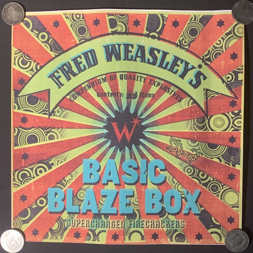 """Plakát inzerující produkt Kratochvilných kouzelnických kejklí: Fred Weasley's Basic Blaze Box (""""Fredova krabice základního ohňostroje"""")."""