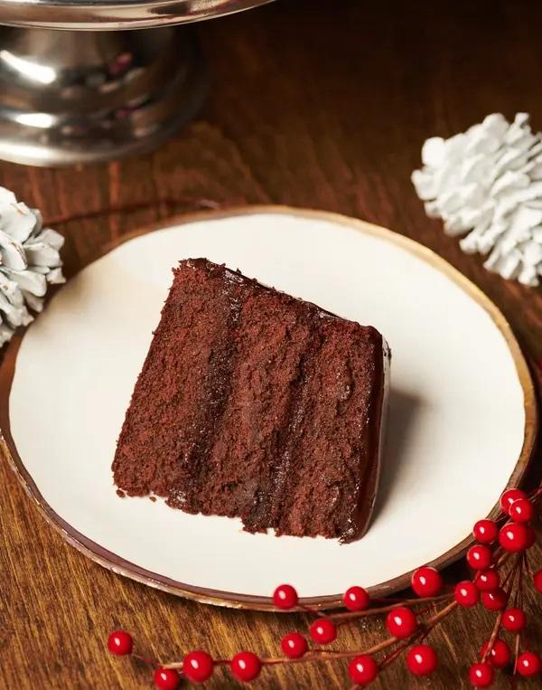 Porce čokoládového dortu na bílém talíři.