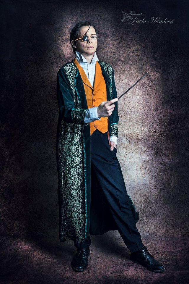 Promo fotka profesora Ladmana z LARPu na motivy Harry Pottera. Profesor má ulízlé kratší tmavé vlasy. Má košili s vyhrnutým límcem, tmavě žlutou vestu, zdobený plášť s květinovým vzorkem na tmavě zeleném pozadí, černé kalhoty a černé boty. Na obličeji má přes pravé oko trojitou souběžnou jizvu sahající od poloviny pravé části čela až po pravou líci (jedna až k pravému koutku úst). Přes pravé oko má ozdobnou klapku z tmavého blyštivého krystalu. Stojí vahou na pravé noze s hůlkou v pohotovostní poloze a levou nohou napjatě nakročenou stranou vpřed.