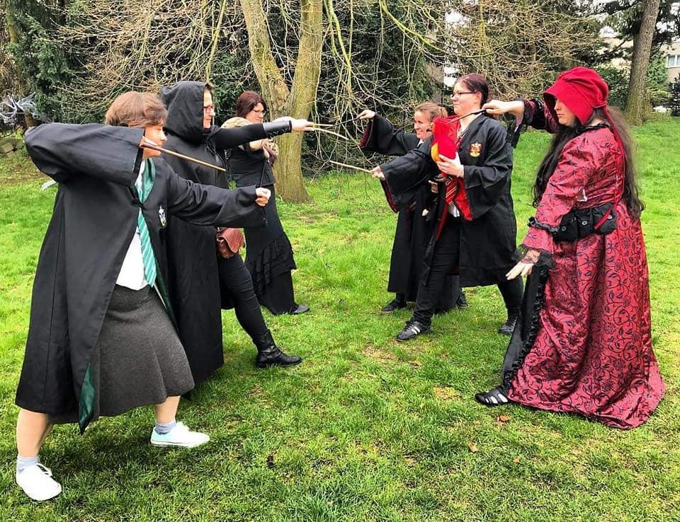 Fotka cvičného skupinového souboje z LARPu na motivy Harry Pottera. Na levé straně v popředí studentka zmijozelu, za ní bystrozorka Trnobranská a za ní profesorka Dočekalová. Proti nim stojí zprava v popředí profesorka Pidimová a za ní doprostřed fotky dvě studentky nebelvíru. Studentky jsou ve svých uniformách. Bystrozorka je v černém plášti s kápí na hlavě, černých přiléhavých kalhotách a černých kotníčkových botách. Má hnědou brašničku přes vpřed nakročenou levou nohu. Profesorka Dočekalová má tmavé červenohnědé krátké vlasy. Má černé šaty až k zemi a černou vestu/korzet. Přes rameno/okolo krku má hada. Profesorka Pidimová má tmavě růžový plášť až k zemi s černým vzorkem ve tvaru lístečků a květů a černým krajkovým lemováním, okolo pasu má černé kapsičky. Má dlouhé rozpuštěné černé vlasy, které unikají z pod tmavě červeného čepce. Všech šest čarodějek na obrázku stojí bokem s hůlkami v pohotovosti napřažené proti soupeři. Jedna studentka nebelvíru navíc v ruce drží fénixe. Souboj se odehrává venku, na zahradě, či příměstském lesíku. Všichni stojí na trávě, za nimi jsou stromy skrz které je špatně vidět mudlovský dům.