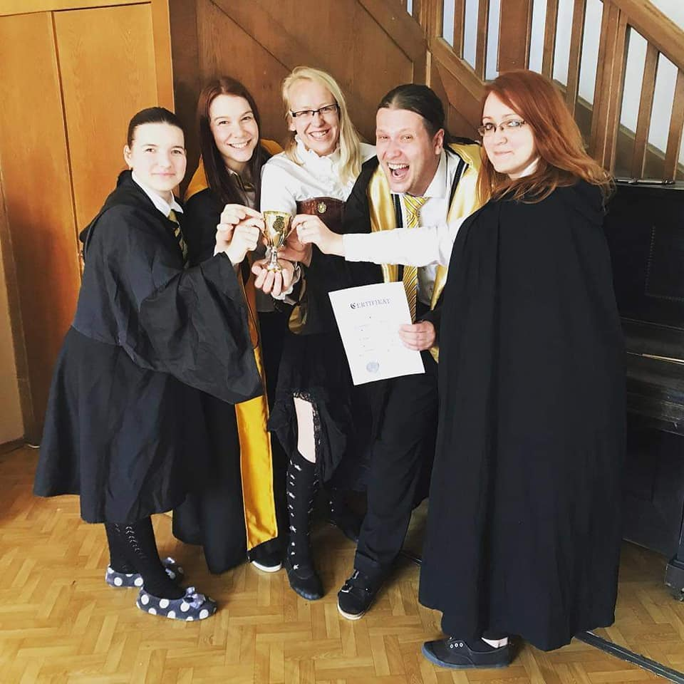 Fotka členů mrzimorské koleje a jejich ředitelky z LARPu na motivy Harry Pottera. Na fotce jsou 3 studentky a 1 student s ředitelkou koleje uprostřed, student je po ředitelčině levici. Studenti jsou v uniformách, všichni jsou šťastní a drží před sebou právě vyhraný školní pohár. Student má navíc v ruce certifikát o absolvování akademie. Ředitelka koleje má rozpuštěné blond vlasy. Je oblečena do bílé košile, hnědého korzetu, černé sukně s krajkovým lemem, černých podkolenek s bílými hvězdičkami a má nazuté černé balerínky. Na obličeji má moderní úzké brýle s černými obručkami. Na korzetu má na pravé straně v úrovni srdce znak Mrzimoru. V pozadí je schodiště a klavír.