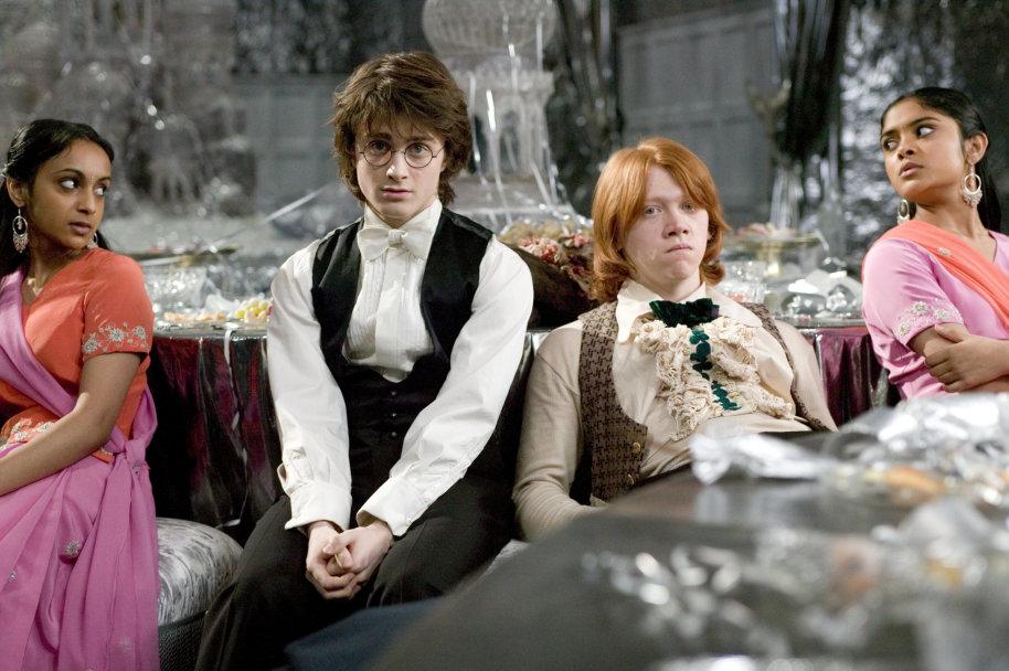 Harry a Ron sedí vedle sebe na vánočním plese znuděně a naštvaně u stolu. Parvati a Padma, sedící vedle svých partnerů na obou krajích fotografie, se na sebe znechuceně dívají.
