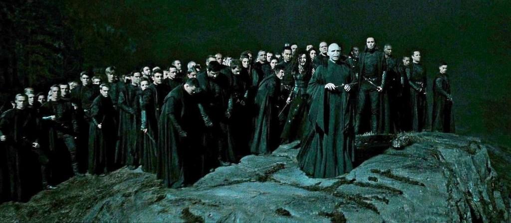 Na skále je hromada Smrtijedů a v popředí stojí Lord Voldemort.
