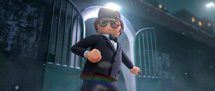 Fotka z filmu Playmobil ve filmu. Postava agenta, kterého dabuje v AJ Daniel Radcliffe stojí před bránou ve zdi. Je oblečený ve smokingu a tváří se bondovsky drsně a sebejistě (tedy alespoň natolik, jak je to možné v případě animované postavičky, která vypadá jako kříženec LEGO postavičky a Igráčka).