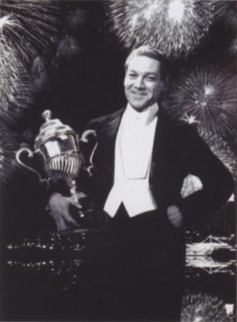 Černobílá fotografie zobrazující mladého Zlatoslava Lockharta s pohárem - oceněním, které získal za své skutky při potírání sil zla. Lockhart je oblečen do smokingu bez kravaty a bílou košilí. Pohár objímá pravou rukou. Na pozadí za ním jsou světla města a na obloze vybuchuje ohňostroj.