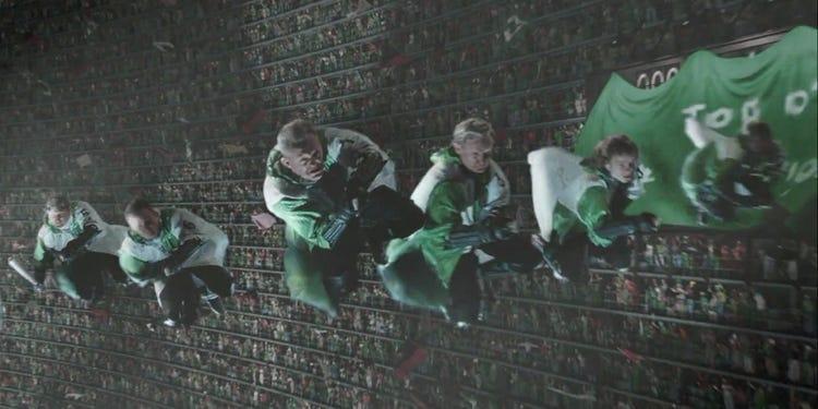"""Scéna z Ohnivého poháru, konkrétně z mistrovství světa ve famfrpálu. Irský národní famfrpálový tým ve svých tradičních zeleno-bílých dresech obkružuje přeplněný famfrpálový stadion. V záběru vidíme jen 6 ze 7 hráčů, kteří letí ve """"V"""" formaci."""