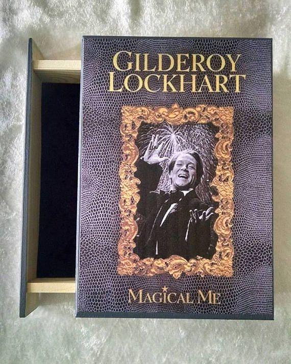 """Na bílém pozadí je obálka knihy s imitací hadí kůže. Uprostřed je černobílá fotografie slavícího Zlatoslava s ohňostrojem nad jeho hlavou. Fotografie je zlatě a bohatě orámovaná. Nad ní je nápis kapitálou """"Gilderoy Lockhart"""" a pod fotografií zlatý nápis """"Magical Me""""."""
