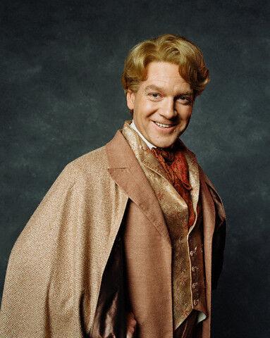 Promo fotka Zlatoslava Lockharta. Přirozeně v jeho stylu. Lockhart je na fotku natočen částečně bokem, ruce pod zlatým pláštěm založené v bok a jeho obličej se dívá přímo na fotografa. Má samolibý úsměv.