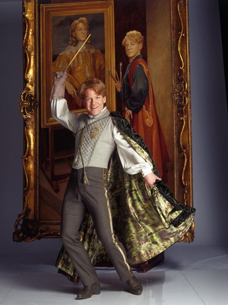 """Profesor Lockhart pózuje před svým vlastním portrétem, na kterém on sám maluje sebe samého. """"Živý"""" Lockhart je oblečen v šedém duelovém úboru a s černo-zlatým pláštěm na jeho pravém rameni, stojí na lehce pokrčené pravé noze, levá noha je posunuta dozadu a špičkou se dotýká země. Levou ruku má napnutou a drží v ní plášť, takže ten vytváří více dojem """"vlání"""". Pravá ruka v rukavici je vzpažena vzhůru a drží v ní svoji hůlku."""