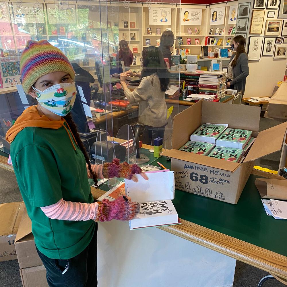 """Dívka s dlouhým copem přehozeným přes levé rameno, v čepici, v roušce a zeleném triku. Dívá se přímo na diváka a přitom  podepisuje knihu """"This Is How We Fly"""" v knihkupectví. Na stole má plnou krabici této knihy."""