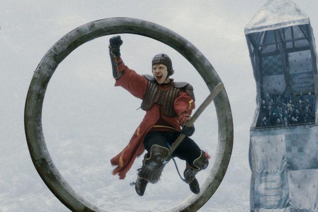 Scéna, kdy se Ron jakožto brankář zakuklený v chráničích raduje před jednou z obručí. Pravou ruku má zdviženou ve vítězném gestu a levou se drží koštěte. Ve tváři má radostný výraz. Famfrpál se odehrává v zimě, na pozadí je bílo a zasněžené havraspárské hlediště.