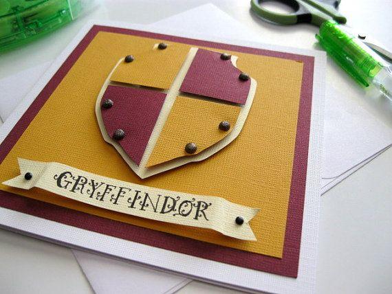 """Na fotografii je nebelvírské přáníčko vyrobené z barevných čtvrtek. Je na něm jednoduchý řerveno-zlatý znak a pod ním nápis """"Gryffindor""""."""