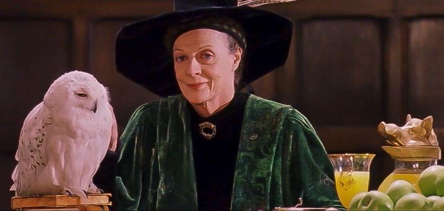 Fotografie z filmu, kdy profesorka McGonagallová v zeleno-černém hábitu sedí u stolu, na němž je pomerančový džus a jablka vpravo na fotografii. Vlevo sedí sova Hedvika na knihách. Profesorka se usmívá na diváka.