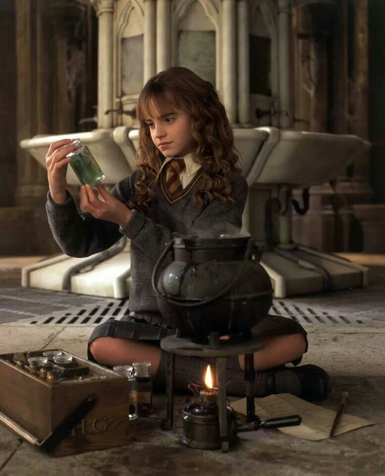 Fotografie ze scény z Tajemné komnaty. Hermiona sedí v tureckém sedu před umyvadly, před ní je na zemi kotlík, v němž je připravován mnoholičný lektvar. Před jejím pravým kolenem je bedna s přísadami. Hermiona drží v obou rukách lahvičku s nazelenalou tekutinou, kterou jsi prohlíží. Na levé straně od kotlíku leží pergamen s poznámkami a svoji hůlku.