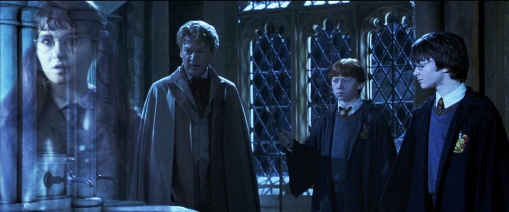 Fotografie z filmu Tajemná komnata, odehrávající se v Uršulině koupelně. Za třemi okny v pozadí je noc. Vedle sebe stojí zleva Zlatoslav Lockhart, dívající se na umyvadla před sebou, vlevo od něj Ron s nataženou rukou, v níž drží hůlku. Úplně vpravo pak stojí Harry, který upírá svůj zrak na umyvadla. Uplně vlevo je pak Ufňukaná Uršula, která odchází ze scény.