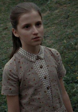 Fotografie z filmu Relikvie Smrti 2: mladá Petunie Evansová. Holčička s dlouhými sepnutými vlasy se dívá kamsi za diváka s vyjeveným výrazem. V pozadí je tráva.