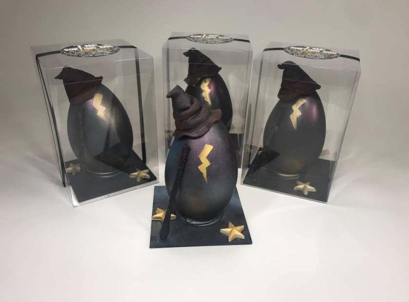 Na fotografii jsou čtyři černá vajíčka s černým kloboukem a namalovaným zlatým bleskem uprostřed každého z nich. V popředí je jedno, které stojí na černém čtvercovém podstavci se dvěma zlatými pěticípými hvězdami. O vejce se opírá koště. Za ním jsou stejná tři vejce v průsvitných krabičkách.