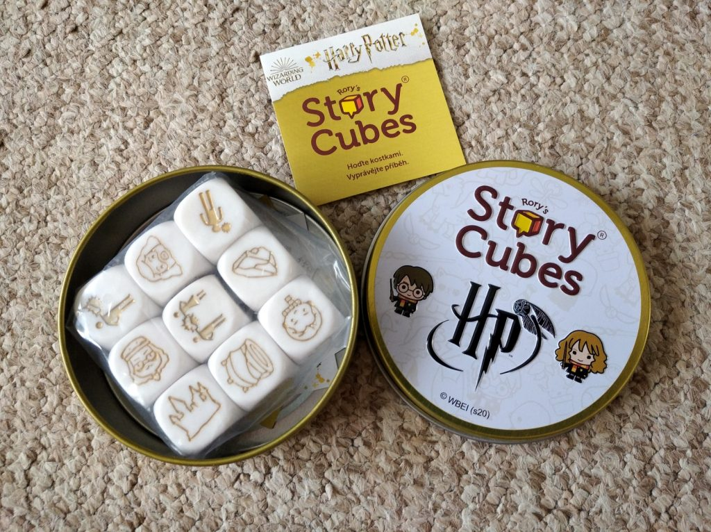 """Na fotografii je otevřená plechová krabička. Vlevo je její spodní díl a uvnitř 9 zabalených bílých kostek se zlaými obrázky. Vpravo je víčko plechovky - nahoře je logo """"Rory's Story Cubes"""" pod ním logo """"HP"""" se zlatonkou. Nalevo od """"HP"""" je chibi Harry a napravo od loga chibi Hermiona. Nahoře mezi oběma díly krabičky je maličký letáček ve zlaté barvě."""