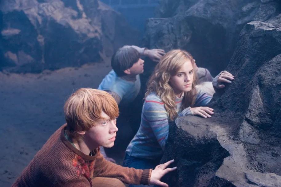 Scéna z filmu Fénixův řád: Ron (v popředí), Hermiona a Neville (nejvíce vzadu) se skrývají za skalky, které jsou rozprostřeny v komnatě smrti na Odboru záhad.